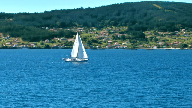 Sailing yacht near green Spanish coast with village video