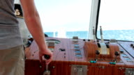 sailor controls boat in the wheelhouse video