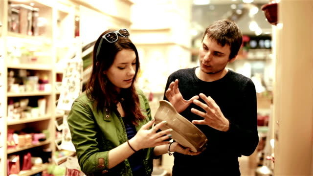 sale, consumerism and people concept shopping - happy young couple choosing dishes in mall video