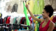 Sale, consumerism: Attractive african american woman chooses clothes in shop video