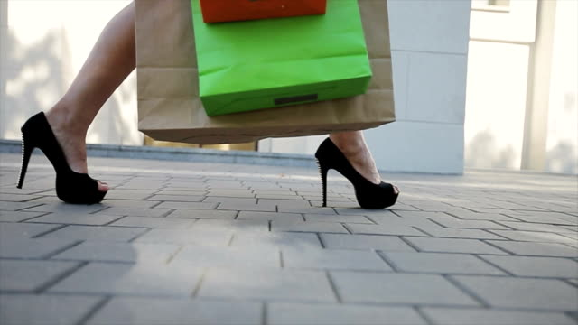 Sale, consumerism: Confident lady at heels with shopping bags video