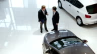 Sales manager and customer in car showroom video
