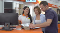 Sales woman showing her customers how to assemble the wooden furniture video