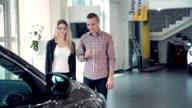 Salesman Talking to Couple inside Car Dealership video