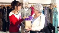 Saleswoman in clothing store helps customer video