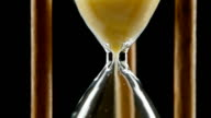 Sand falls through a bottleneck in a hourglass. Black. Close up video