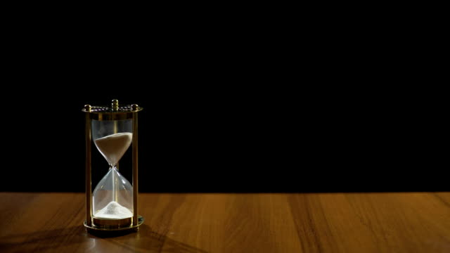 Sand flowing fast in hourglass on table against black background, time flies video
