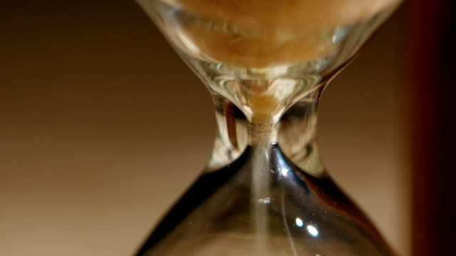 Sand flowing through an hourglass. Close up video