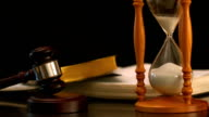 Sand flowing through hourglass beside gavel and bible video