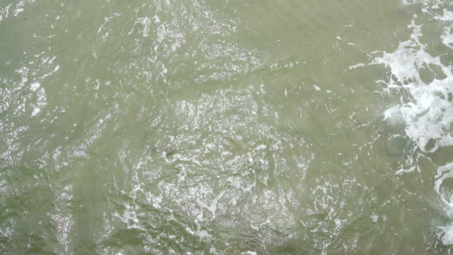 Sandy Beach with Wave to cover and fall down, bubble on surface and spiral clear water video