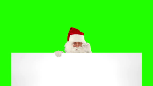 Santa Claus appears behind a white sheet with space for tex Green Screen video