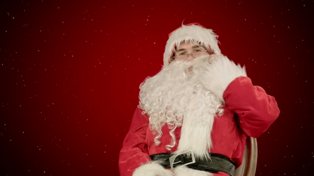 Santa Claus calling with a mobile phone on red background with snow video
