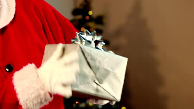 Santa claus checking a gift box and smiling video