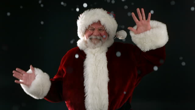 Santa Claus dancing in the falling snow, slow motion video