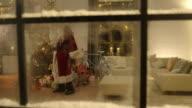 Santa Claus distributing presents under the christmas tree video