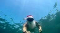 Santa Claus diver spending Christmas vacation at tropical beach resort snorkeling underwater video