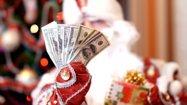 Santa claus, father christmas, father frost chooses what is better to give money dollars or a Christmas gift in a colorful paper wrapper with a gold bow as a present for Christmas or new year, in the background is a Christmas tree video