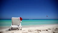Santa Claus Hat on sunbed near  tropical calm beach with turquoise caribbean sea water and white sand video
