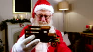 Santa claus holding and looking at a toy car video