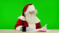 Santa Claus is Reading a Wish List and Makes Notes video