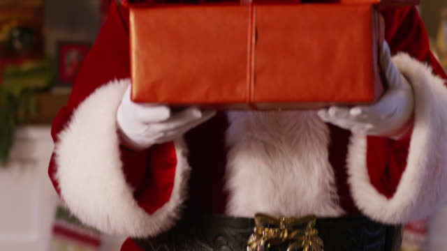 Santa Claus peeks out from behind stack of gifts video