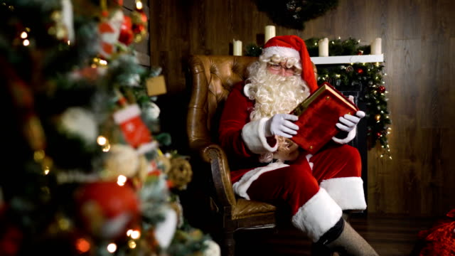 Santa Claus pulling out old red silk album near christmas tree with toys and lights video
