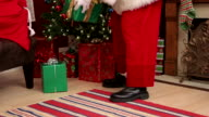 Santa Claus putting gifts under Christmas tree video