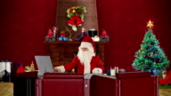 Santa Claus reading letters and sorting presents, office with Christmas decorations video