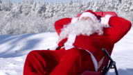 Santa Claus relaxing in a snowy forest at winter ski resort video
