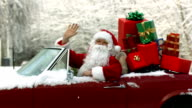 Santa Claus sitting in convertible piled with Christmas gifts video