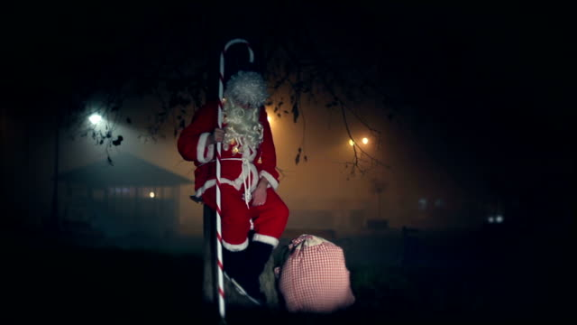 Santa Claus swinging on a swing, night, sack with gifts, stick, tree, chrismtas, gift, city, video