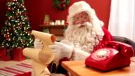 Santa Claus talking on retro telephone video