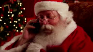 Santa Claus talks on cell phone video