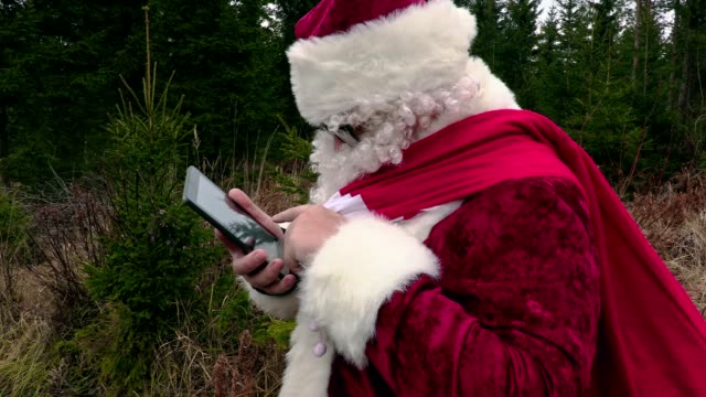 Santa Claus using tablet and laughing video