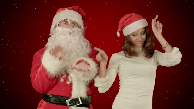 Santa claus with beautiful dancing girl on red background with snow video