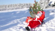 Santa Claus with gift bag using tablet computer in snow covered winter forest video
