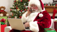 Santa Claus with laptop and cell phone video