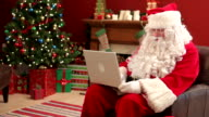 Santa Claus working on laptop computer video