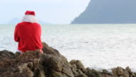 Santa clause sitting dance on the rock sea video