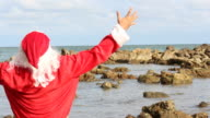 Santa clause stretch the arms and laughing near the rock beach video