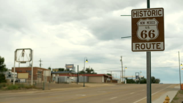 4K  Santa Rosa, New Mexico Historic Route 66 road sign cars drive by clouds video