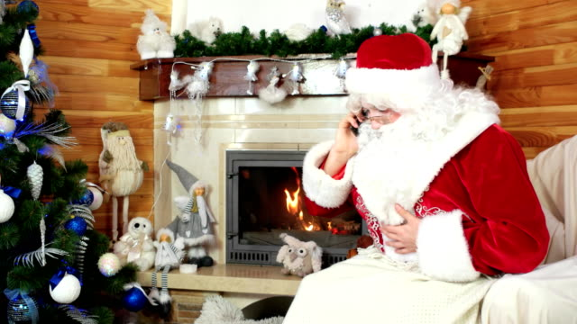 santa talking on cell phone, santa claus wishing merry christmas on phone, using electronic device video