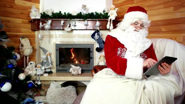 santa using tablet, saint nicolas choosing christmas gifts for children in internet, celebration video