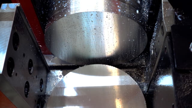 Saw cuts off part of the round metal workpiece and cooled by coolant video