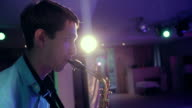 Saxophone player performs on stage with professional light. video