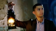 Scared young man in a dark hallway, holding an oil lamp in his hand. Dressed in a suit video