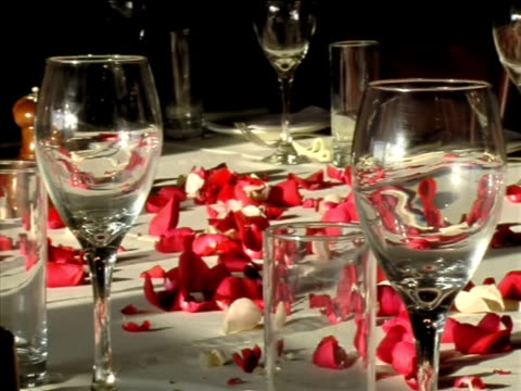 Scarlet rose petals anf glasses on the table video