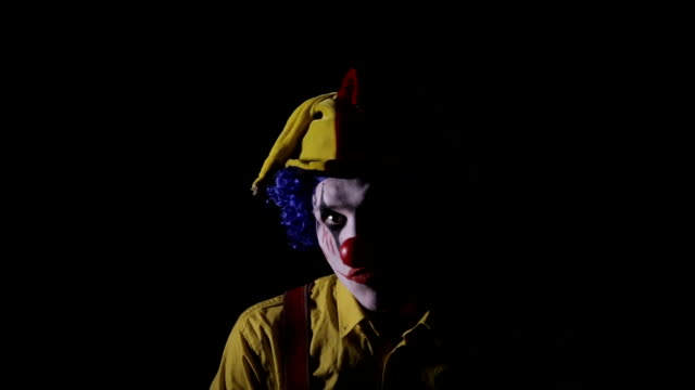 Scary clown making frightening faces. Close-up video