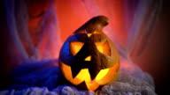 Scary Halloween Pumpkin looking through the smoke. Glowing, smoking monster pumpkin from depths of hell video
