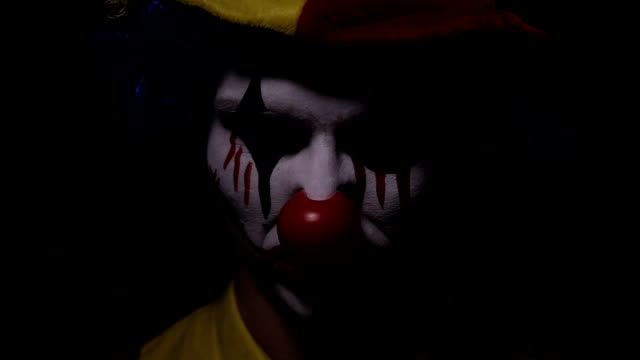Scary shot of a screaming spooky mad clown. Portrait video
